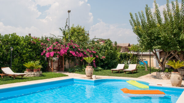 A bright blue swimming pool with floating loungers atop. Bright green foliage surrounds the pool along with bright purple flowers.